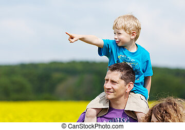 little boy sitting on his fathers shoulders