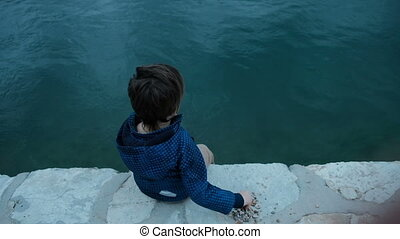 Little boy sitting on pier throws stones into water outdoors.
