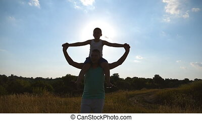 Little boy sitting on shoulders of his daddy and playing raised hands as airplane at sunset. Happy father and son playing on the field at sunny day. Dad and child having fun together. Slow motion