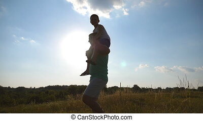 Little boy sitting on shoulders of his daddy while walking at beautiful landscape. Father and son playing on the field at sunset. Happy family spending time outdoors. Active lifestyle. Slow motion