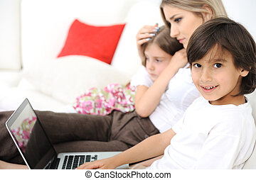 Little boy sitting on sofa with his mother and sister and using laptop