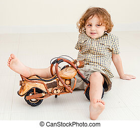 little boy sitting on the floor and playing toy motorcycle