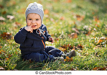 little boy sitting on the grass