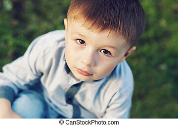 little boy sitting on the grass in park outdoors