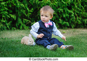 little boy sitting on the grass with a rabbit