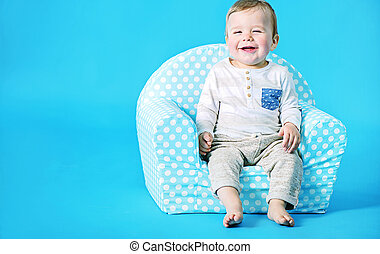 Little boy sitting on the toy armchair