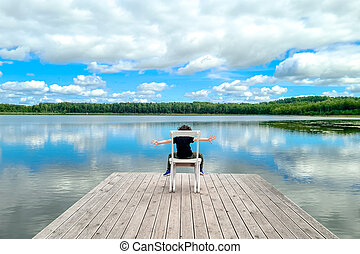 Little boy sitting on white empty deck chair at the lake dock.