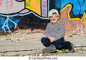 Little boy sitting sulking with a pouting expression on the...