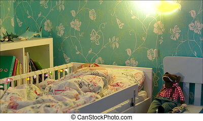 Little boy sleeping and turning off bedside lamp