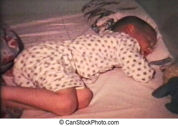 A cute little boy sleeps soundly in his bed all cozy. (Scan from archival 8mm film)