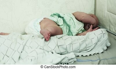 Little boy sleeping on sofa. Crying baby girl on other side of bed with dummy.