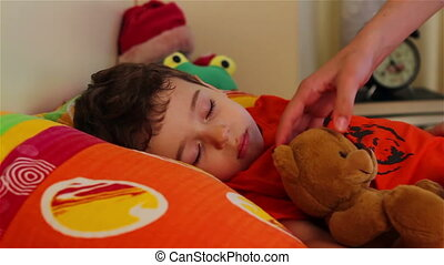 Little boy sleeping with his teddy