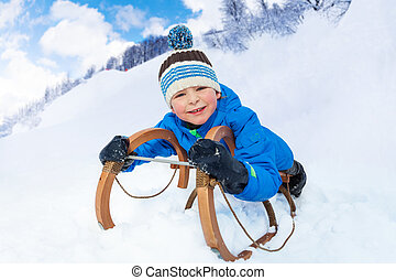 Little boy  slide down laying on sledge smile