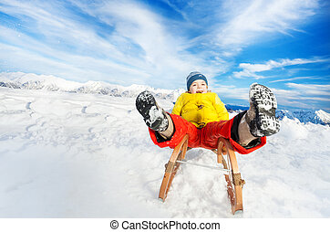 Little boy slide down on sledge legs first