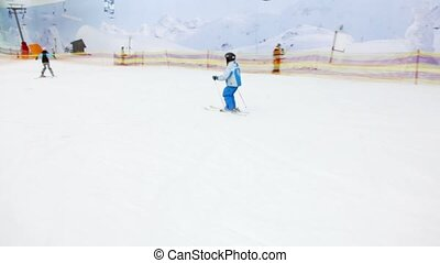 Little boy slides on alpine skis from snowy slope, shown in...