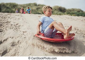 Little Boy Sliding Down a Sand Dune