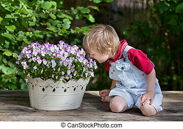 Little boy smelling the flowers