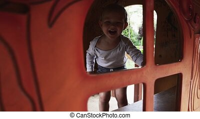 Little boy smile in camera from wooden home on playground. Summer day. Walking