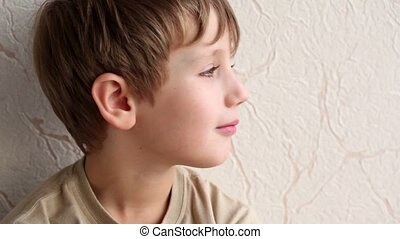 little boy smile on background of wall covered with wallpaper, closeup view