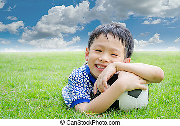 Little boy smiles with his football