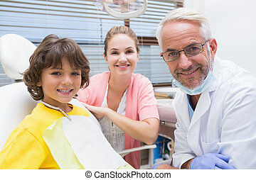 Little boy smiling at camera with mother and dentist beside ...