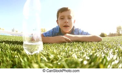 little boy soccer player sport drinks water from a plastic...