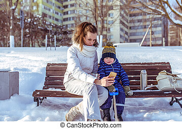 Little boy son 2-3 years old, sitting bench in winter city. Woman mom in hands of phone, taking pictures, online app in social networks. Nature winter snowy afternoon cup of tea with a thermos.