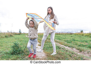 Little boy son 3-5 years old, runs, runs, kite. Woman mom plays with her son, happy play having fun, in autumn on the green grass in warm clothes.
