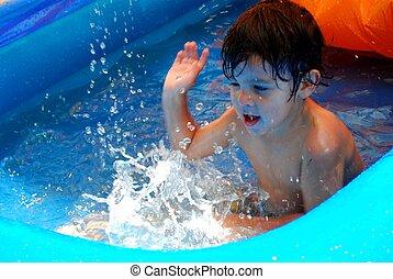 Little boy splashing in a pool