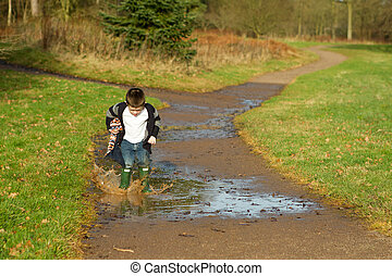 little boy splashing in a puddle