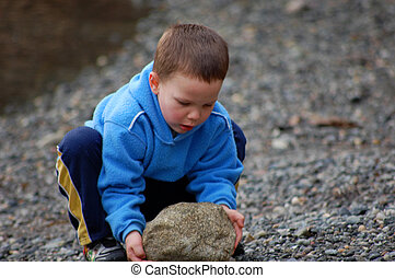 Little Boy Squatting to Pick Up Large Rock - Little boy is ...