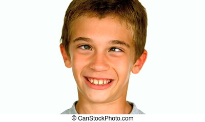 Little boy squinting against white background