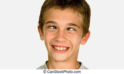 Little boy squinting against white background in slow motion...