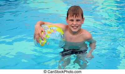 Little boy stand in pool and hold inflated ball with earth...