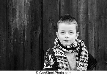little boy standing against a wooden background