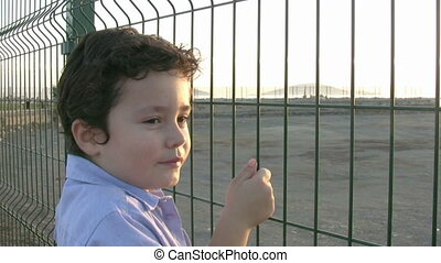 Little boy standing at the fence