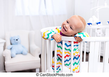 Little boy standing in bed - Cute laughing baby standing in...
