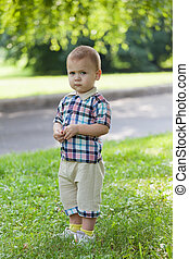 little boy standing in the grass on a summer day