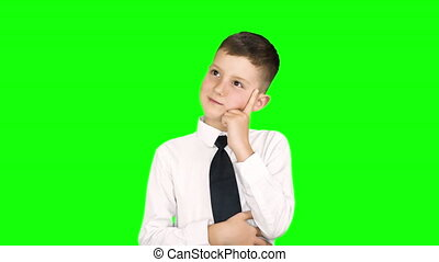 Little boy standing in the studio in front of a green background shows different emotions. Shot over green screen.