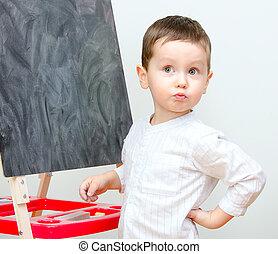 Little boy standing near blackboard