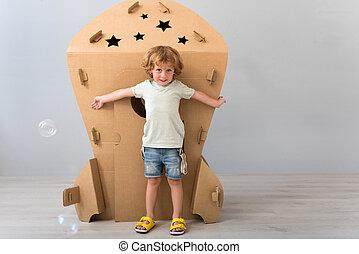 Little boy standing near carton rocket