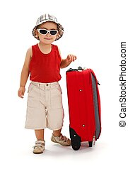 Little boy standing near luggage, ready for journey