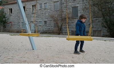 Little boy standing near swing in playground outdoors.