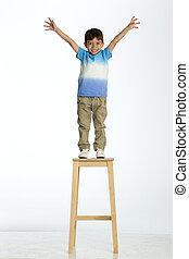 Little boy standing on a high stool