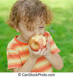 little boy standing on the grass and holding apple