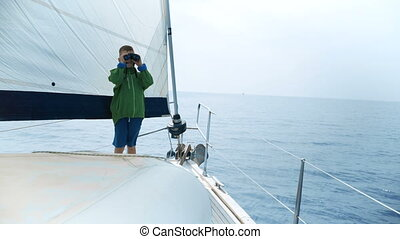 Little boy stands on a yacht and looks in a binocular