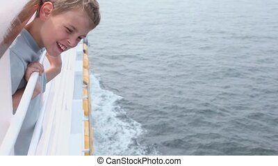 Little boy stands on deck near fence and watches on waves