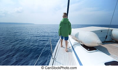 Little boy stands on the bow of the yacht and shows the way