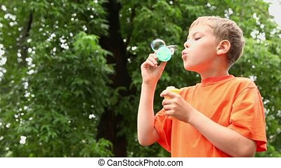 Little boy stands under rain and blows soap bubbles near tree