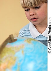 Little boy staring at globe
